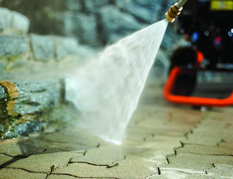 Pressure washing machine spraying a patio